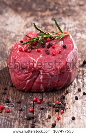 raw steak with pepper on wood - stock photo