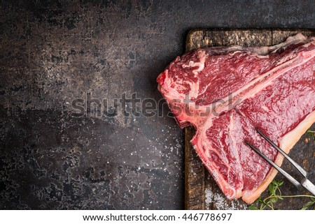 Raw T-bone Steak for grill or BBQ with meat fork on aged cutting board and dark rustic metal background, top view - stock photo