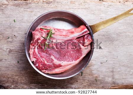 raw t bone steak in a copper pan - stock photo