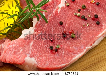raw T-bone with rosemary and pepper - stock photo