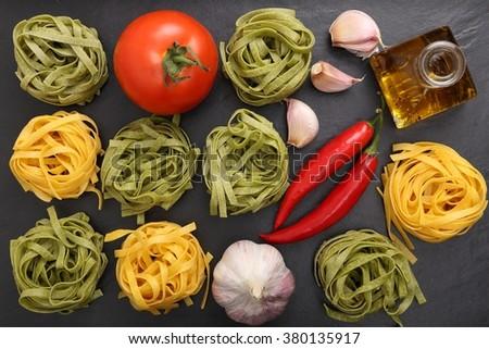 Raw tagliatelle pasta on the black ceramic background. - stock photo