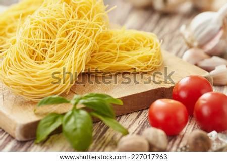 raw tagliolini on a chopping board - stock photo