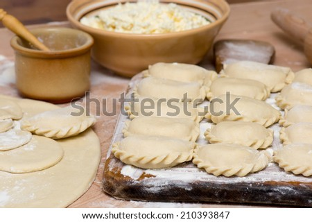 Raw traditional Ukrainian hand-made varenyky (dumplings) (pierogi ruskie in Poland) with cottage cheese - stock photo