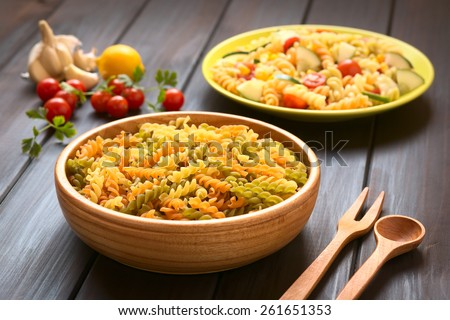 Raw tricolor fusilli or rotini pasta (traditional, tomato, spinach taste) in wood bowl with pasta salad, ingredients photographed with natural light (Selective Focus, Focus one third into the pasta)  - stock photo