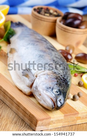 Raw trout on the chopping board with lemon and spices - stock photo