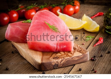 Raw tuna fillet with dill, lemon and cherry tomatoes in olive cutting board - stock photo