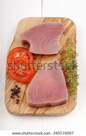 raw tuna fillet with tomato slice, pepper and thyme on wooden board - stock photo