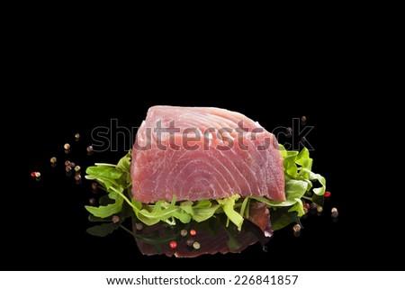 Raw tuna steak isolated on black background. Traditional seafood eating. Sashimi sushi. - stock photo