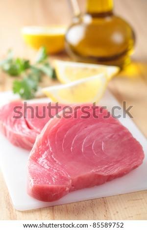 Raw tuna steaks on a cutting board - stock photo