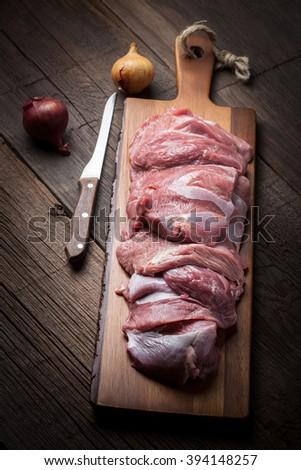 Raw turkey meat on a wooden chopping board. Dark light. - stock photo