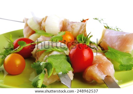 raw uncooked chicken shish kebabs with tomatoes on metal steel skewers on green plate isolated over white background - stock photo