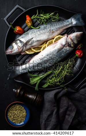 Raw uncooked seabass fish with herbs and spices in cast iron cooking pan on black wooden background. Top view, dark concept - stock photo