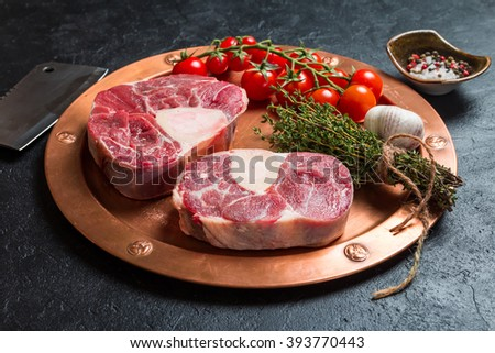 Raw veal shank slices meat and ingredients for Osso Buco cooking on black background, top view - stock photo