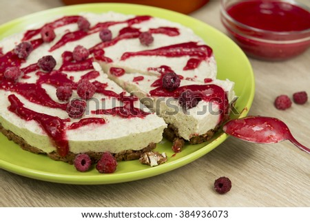 Raw vegan berry cheesecake gluten-free with the frozen raspberry and raspberry sauce on a bright wooden background. Fully raw food. - stock photo