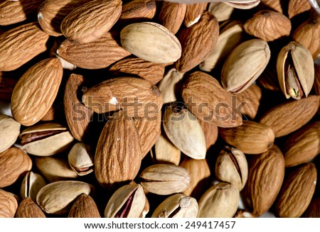 Raw vegan nuts background - almonds and pistachio - stock photo