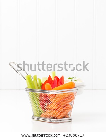 Raw vegetables and dip in a fryer basket suggesting an alternative to greasy fried foods. - stock photo