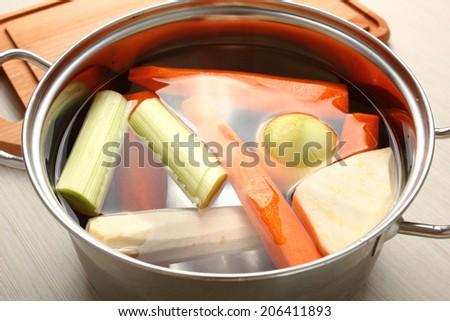 Raw Vegetables in saucepan. Making vegetables bouillon. - stock photo