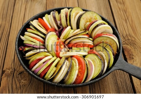 Raw vegetables layed for ratatouille made of eggplants, squash, tomatoes and onions in black cast iron pan on wooden table horizontal - stock photo