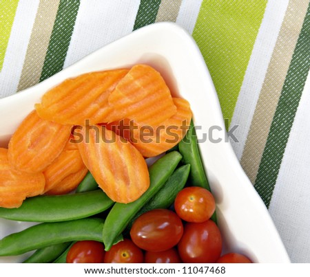 Raw vegetables to eat with dip including carrots, sugar snap peas, and tomatoes. - stock photo