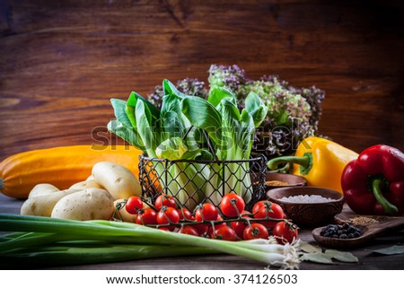 Raw vegetables with spices on wooden table - stock photo