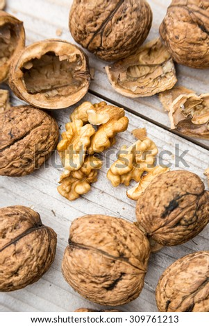 Raw walnuts on wooden bench - stock photo