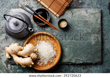 Raw white rice, green tea teapot, soy sauce and sushi chopsticks on gray stone slate background - stock photo