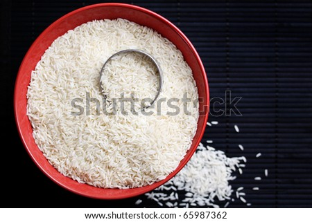 Raw white rice in a red bowl on a dark background. - stock photo