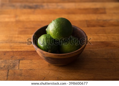 Raw whole limes in bowl on rustic wood with copyspace - stock photo