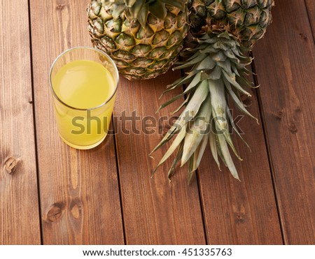 Raw whole pineapple with glass of juice on wooden brown surface table - stock photo