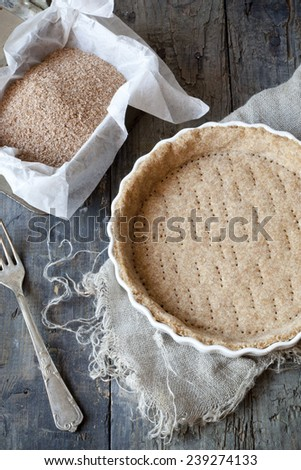raw wholemeal dough for tart on ceramic mold for quiche on table with fork and flour on box - stock photo