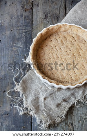 raw wholemeal dough for tart on ceramic mold for quiche on wooden table with napkin - stock photo
