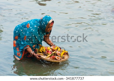 RAXAUL, INDIA - NOV 9: Unidentified Indian woman celebrating Chhath by standing in a river and offering prashad (prayer offerings) to the rising sun on Nov 9, 2013 in Raxaul, Bihar state, India. - stock photo