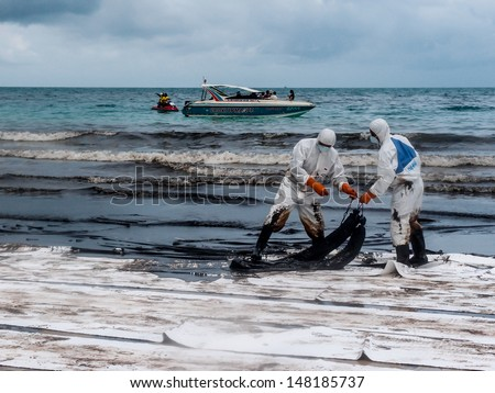 RAYONG -JUL 31: officers use absorbent boom to correct oil in the water on Jul 31, 2013 in Rayong, Thailand. 50 tons of oil came from the accidental leaking during transferring from tanker on July 27. - stock photo