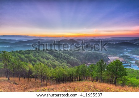 Rays early in Da lat highland pine forest with sun through sky like a giant fan from horizon, beneath pine forest and villages in countryside prepares to welcome new day peaceful - stock photo