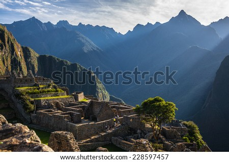 Rays of light at Machu Picchu, Peru. As the sun rises the ruins look golden warm. - stock photo