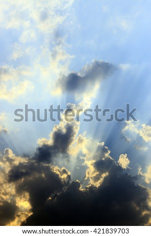 Rays of light shining through clouds storm, over light - stock photo