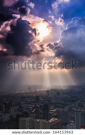 Rays of light shining through dark clouds city Bangkok, Thailand - stock photo
