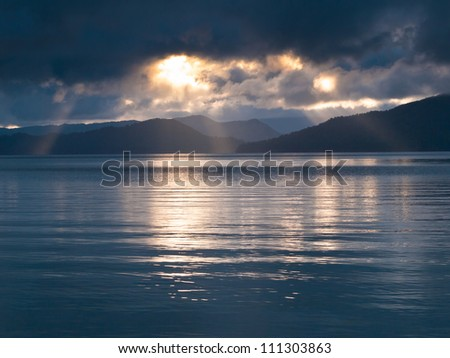 Rays of sun shining through the clouds and sunset over water - stock photo