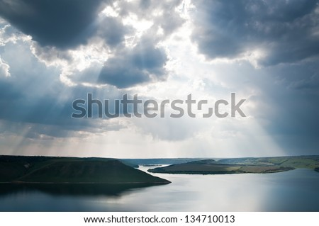 Rays of sun shining through the clouds. The river runs into the distance. The river is calm. The sky is cloudy. - stock photo