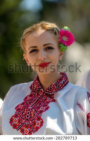 "RAZLOG, BULGARIA - APRIL 13, 2015: A beautiful female Bulgarian folklore dancer posing during the traditional folklore festival ""1000 national costumes"" - stock photo"