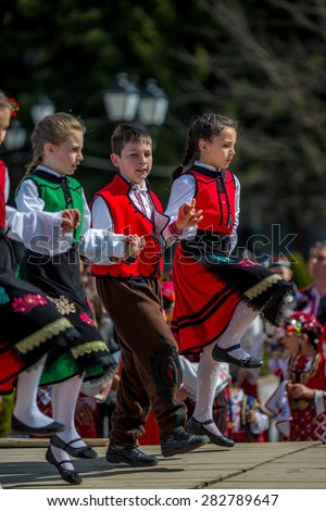 """RAZLOG, BULGARIA - APRIL 13, 2015: Bulgarian children dancing on the stage during the traditional folklore festival """"1000 national costumes"""" - stock photo"""