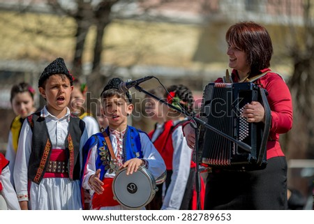 """RAZLOG, BULGARIA - APRIL 13, 2015: Bulgarian children performing a song with their music teacher on the stage during the traditional folklore festival """"1000 national costumes"""" - stock photo"""