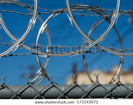 Razor barbed wire security fence in Los Angeles. Closeup. - stock photo