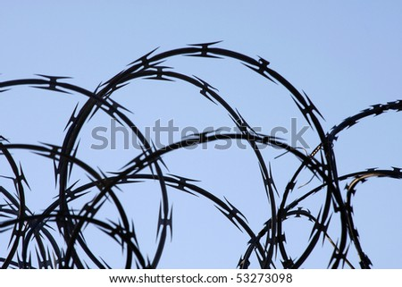 Razor wire against a light blue sky - stock photo