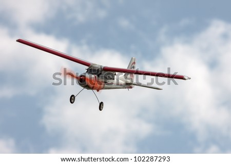 RC model airplane flying in the blue sky, closeup - stock photo
