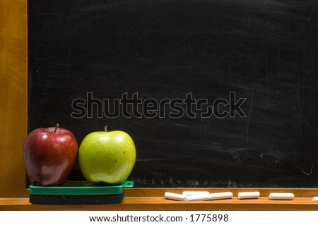 rea and green apple on chalkboard ledge at school, add text to chalkboard - stock photo