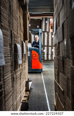 reach truck driver in a warehouse with lots of copy space - stock photo
