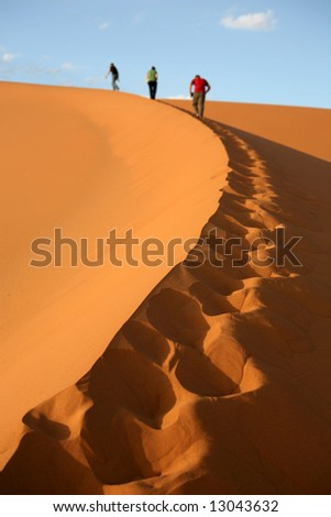 Reaching the top of the Sand Dunes in the Sahara - shallow dof - stock photo