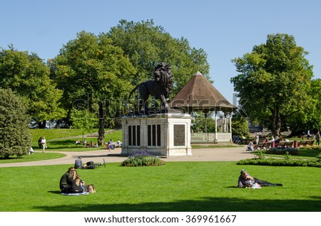 READING, BERKSHIRE - SEPTEMBER 10, 2015: People enjoying the sunshine in Forbury Gardens in Reading, Berkshire.  The Maiwand Lion war memorial dominates the lawns with flower beds and trees. - stock photo
