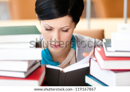 Reading book female student surrounded with piles of books at the library. Training process - stock photo